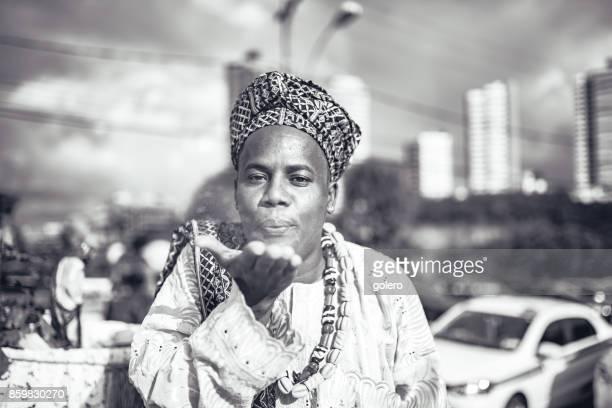 Afro-brasilianischen Mann in religiöser Tracht weht Pulver aus der hand