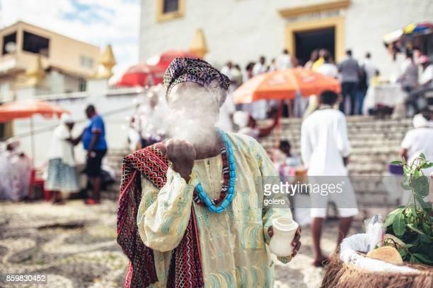 Afro-brasilianischen Mann in religiöser Tracht weht weißes Pulver aus der hand