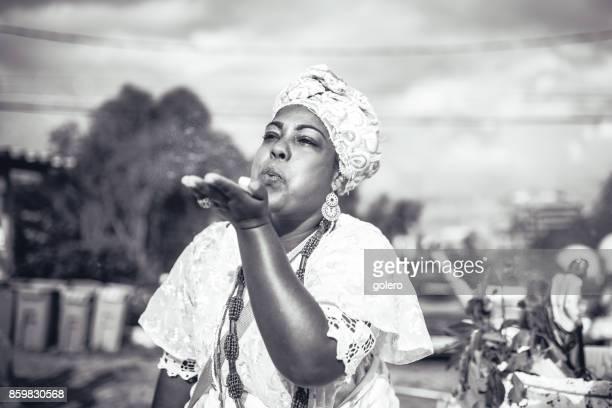 Afro-brasilianische Frau in religiöser Tracht weht Pulver aus der hand