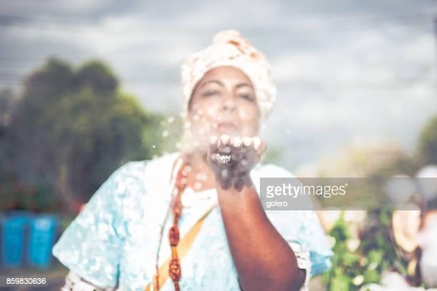 Afro-brasilianische Frau in religiöser Tracht weht weißes Pulver aus der hand