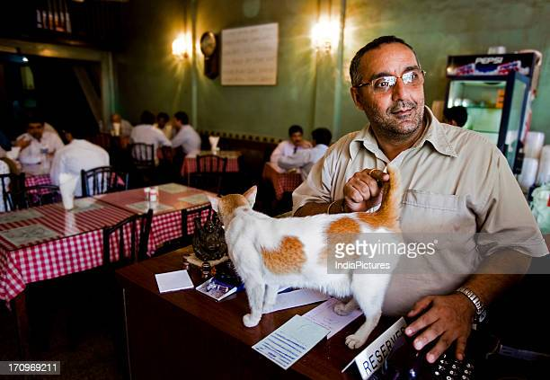 Afshin Kohinoor looks out of the cash counter as he pets his cat during the busy lunch hour at the Brittania Restaurant a Parsi eating joint in the...