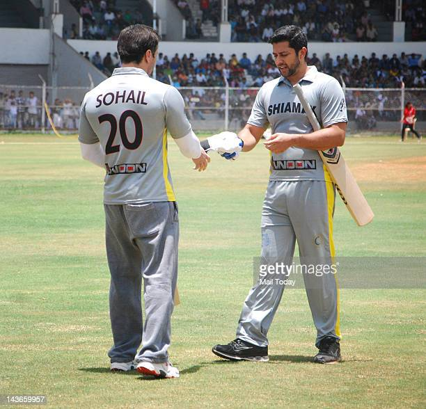 Aftab Shivdasani gives batsman gloves to Sohail Khan during a charity match between celebrities and a team of physically challenged persons to raise...