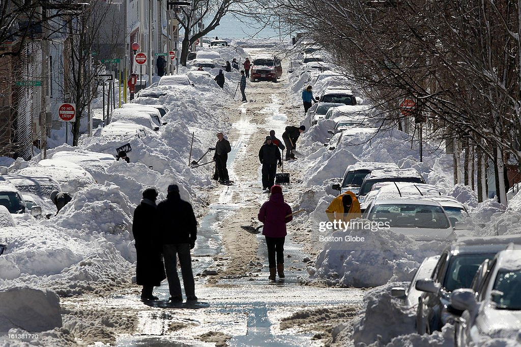 After a blizzard hit New England, residents dig out from the storm, shoveling snow from around their cars on N Street in South Boston, Feb. 10, 2013.
