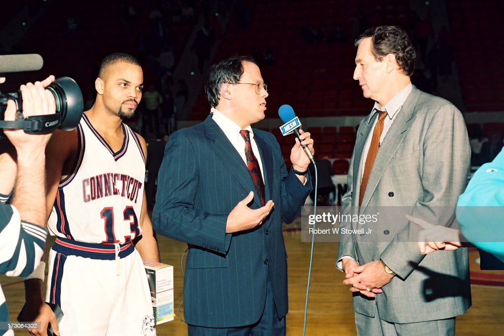 After a game, sports journalist Joe D'Ambrosio (center) of NESN interviews University of Connecticut basketball coach <a gi-track='captionPersonalityLinkClicked' href=/galleries/search?phrase=Jim+Calhoun&family=editorial&specificpeople=208977 ng-click='$event.stopPropagation()'>Jim Calhoun</a> (right) as player Chris Smith (left) watches, Hartford, Connecticut, 1994.