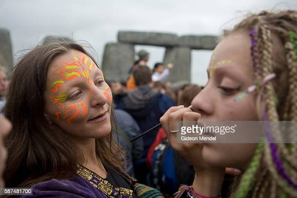 After a night of partying in the stone circle of Stonehenge to welcome the sunrise and celebrate the summer solstice a newage hippy paints mystical...