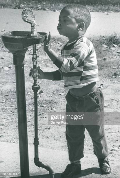 After a refreshing drink Tracey Thompson son of the Leroy Thompsons of 4050 Steele St enjoys the gurgling laughter of the water fountain in the...