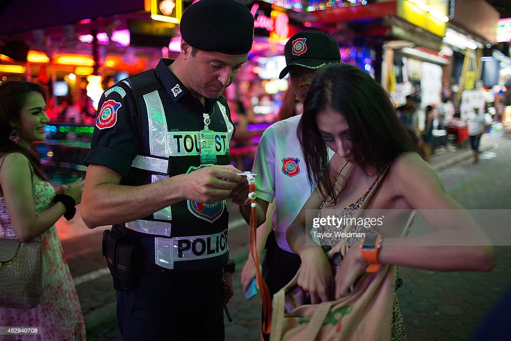 After a robbery is reported, Leo Oner, a member of the FTPA, checks the ID of a transgender woman on Pattaya's Walking Street on July 31, 2014 in Pattaya, Thailand. Since 2002, members of the Foreign Tourist Police Assistants (FTPA) of Pattaya have been assisting local police on Walking Street, Pattaya's main nightlife area. Members of the FTPA carry handcuffs, batons, and pepper spray, and are charged primarily with assisting foreign visitors and the Thai police, as well as breaking up fights and catching thieves.