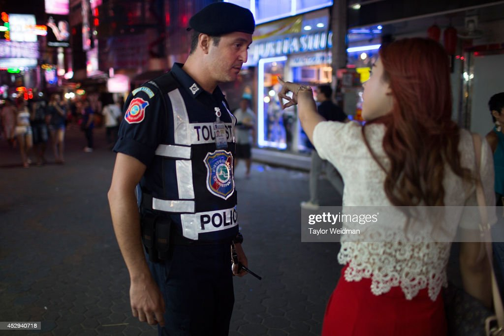 After a robbery, Leo Oner, a member of FTPA, talks with a woman on Pattaya's Walking Street on July 31, 2014 in Pattaya, Thailand. Since 2002, members of the Foreign Tourist Police Assistants (FTPA) of Pattaya have been assisting local police on Walking Street, Pattaya's main nightlife area. Members of the FTPA carry handcuffs, batons, and pepper spray, and are charged primarily with assisting foreign visitors and the Thai police, as well as breaking up fights and catching thieves.
