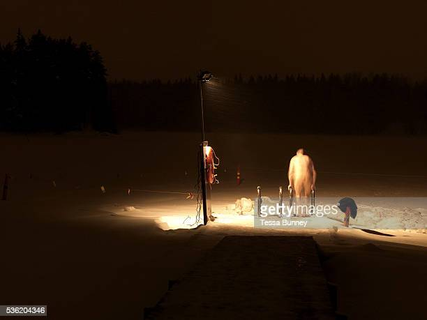 After a sauna a man gets into the hole cut into a frozen lake for iceswimming Kallavesi Kuopio Central Finland Ice swimming takes place in a body of...