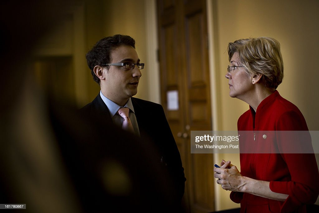 After a Senate Banking Committee hearing, Senator Elizabeth Warren works with staffer, Jon Donenberg, outside the Senate caucus luncheon on Capitol Hill Thursday, February 14, 2013.