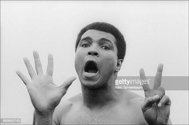 After a workout at his training camp Muhammad Ali holds up seven fingers to signify the number of rounds in which he would defeat his next opponent...
