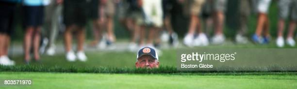 After blasting out of a gren side sand trap on the 2nd hole Mark Calcavecchia peers above the grass line to see where his ball went during the first...