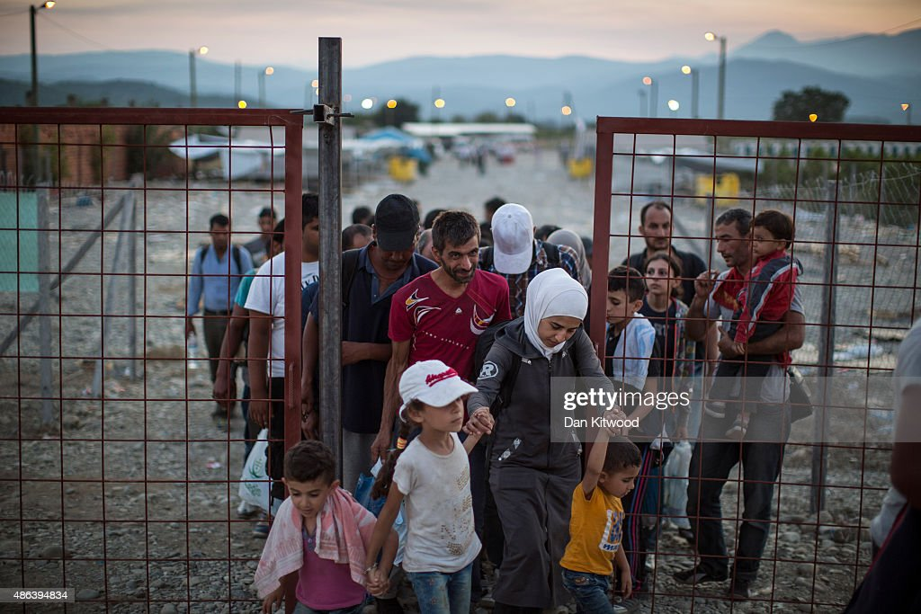 After crossing the Greek Macedonian border and having papers processed, migrant families walk out of a transit area towards Gevgelija train station to find transport North to the Serbian border on September 3, 2015 near Gevgelija, Macedonia. Since the beginning of 2015 the number of migrants using the so-called 'Balkans route' has exploded with migrants arriving in Greece from Turkey and then travelling on through Macedonia and Serbia before entering the EU via Hungary. The number of people leaving their homes in war torn countries such as Syria, marks the largest migration of people since World War II.