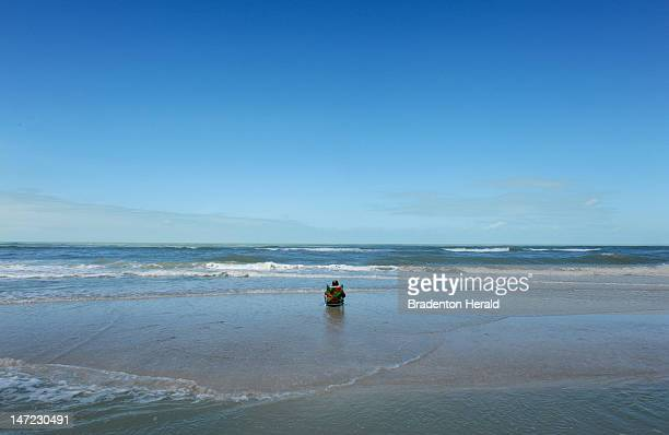 After days of high winds and rain from Tropical Storm Debby a man relaxes Wednesday June 27 on the beach under bright clear blue skies