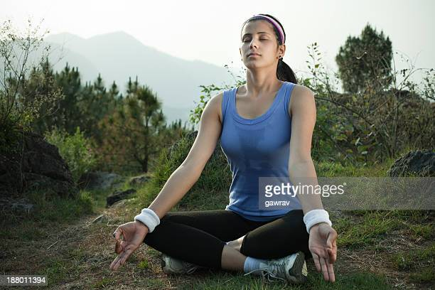 After fitness workout a young woman doing meditation in nature.