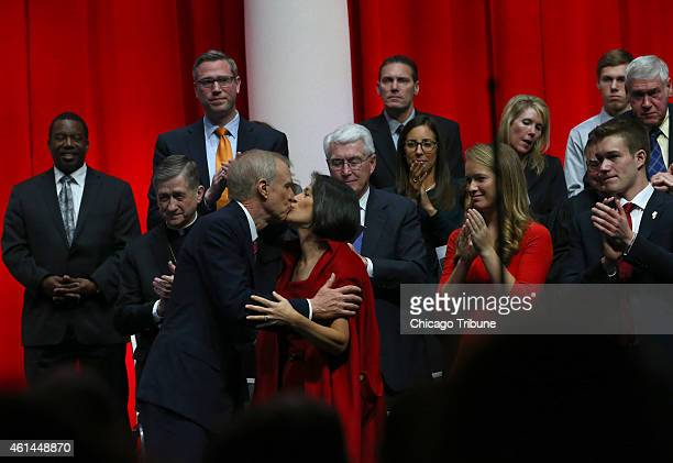 After giving his speech Gov Bruce Rauner kisses his wife Diana while behind him stand Archbishop Blase Cupich and former governor Jim Edgar on Monday...