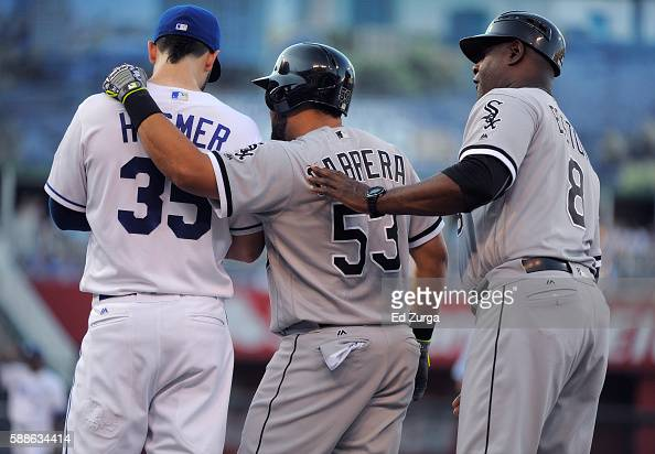 After hitting a single Melky Cabrera of the Chicago White Sox talks with Eric Hosmer of the Kansas City Royals and first base coach Daryl Boston of...