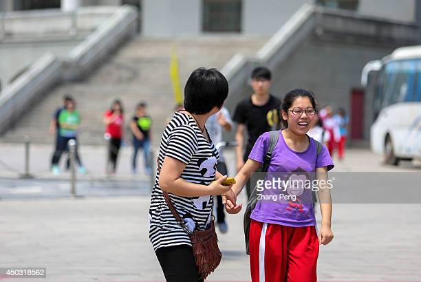 After hours of waiting outside a mother rushes to get her daughter who has just finished her exam For most common Chinese parents supporting children...