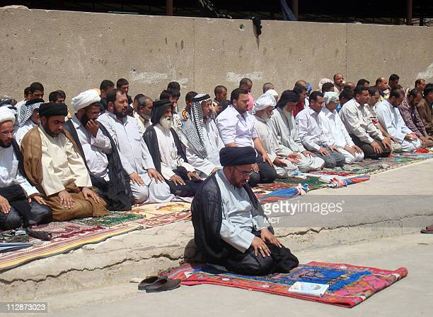 After leading thousands of Sadr City residents in a sermon Sheik Mohanned alMosawi leads followers in prayer Friday July 18 2008 Behind them is a...