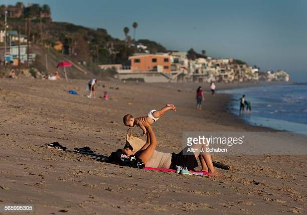 After parking her car along Pacific Coast Highway for free Trina Harris plays with her five–month–old baby daughter Charina Harris of Calabasas on a...