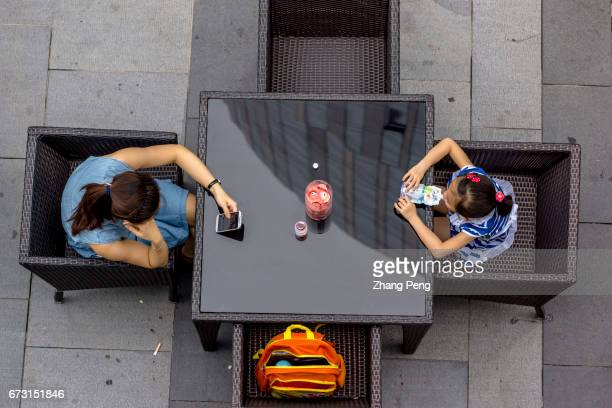 After receiving her daughter from school a mom takes a rest at a roadside table and reads on her smart phone In China the sales of smart phone have...