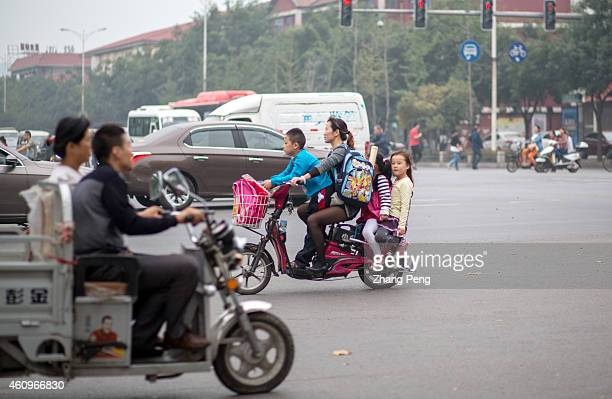 After school parents ride ebikes taking children back home China now has an in excess of 130 million ebikes on its town and city roads creating...
