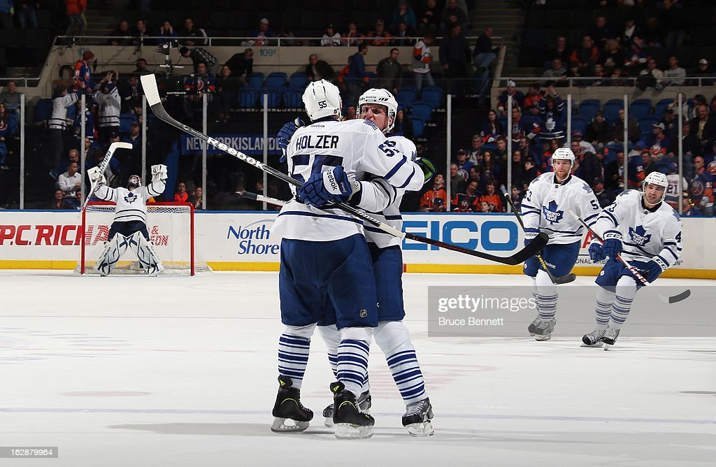 After scoring the winning goal in overtime, Dion Phaneuf #3 of the Toronto Maple Leafs celebrates with Korbinian Holzer #55 in the game against the New York Islanders at the Nassau Veterans Memorial Coliseum on February 28, 2013 in Uniondale, New York. The Leafs defeated the Islanders 5-4 in overtime.
