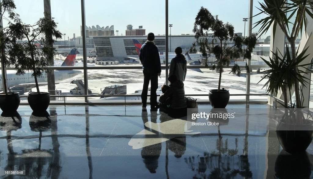 After seeing a family member off, the Villamil family of Boston (two sitting on floor) pause to watch plane activity as Logan Airport is reopened for the first full day, on Sunday, February 10, 2013, after the blizzard.