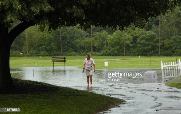 After several storms moved through the area causing havoc around the flooded course a volunteer makes her way back to the clubhouse during the second...