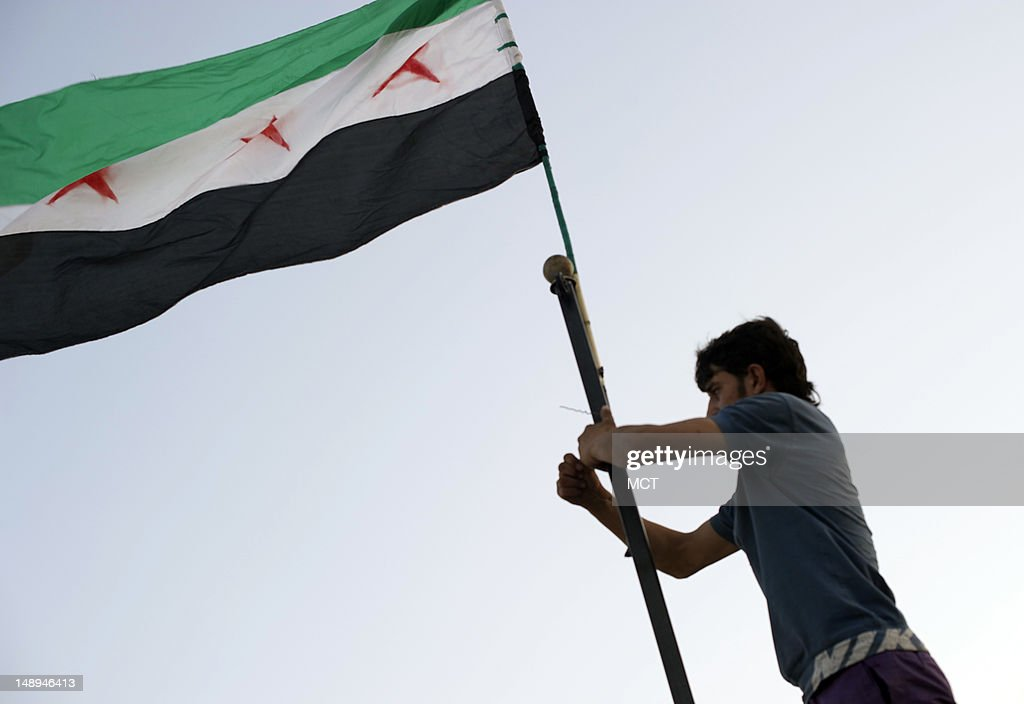After striking the government flag a rebel fighter raises the threestarred revolutionary flag over a captured government position in Al Tal Syria...