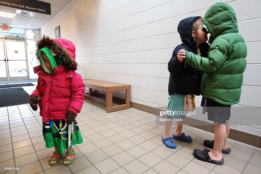 After swimming at the Oak Square YMCA, Rachel Faintuch, 3, and her brothers, Jonathan, 5, and David, 7, right, were bundled up with coats over their towels to guard against the cold. The Oak Square YMCA just broke a record for new memberships in a month with 596 in January.