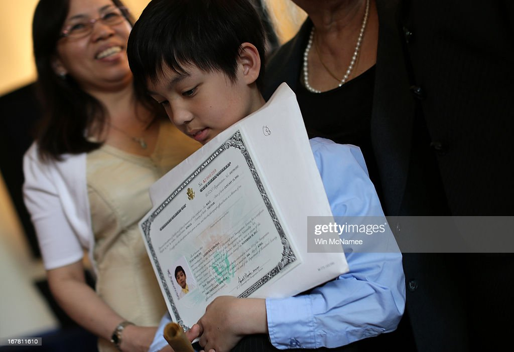 After taking the Oath of Allegiance and becoming a U.S. citizen, Tuan Minh Do holds his certificate of citizenship following a naturalization ceremony for twenty children in the Emancipation Room at President Lincoln's Cottage April 30, 2013 in Washington, DC. The special citizenship ceremony was hosted by the U.S. Citizen and Immigration Services at the seasonal residence the Lincoln family used during the Civil War and the site where President Lincoln developed the Emancipation Proclamation.