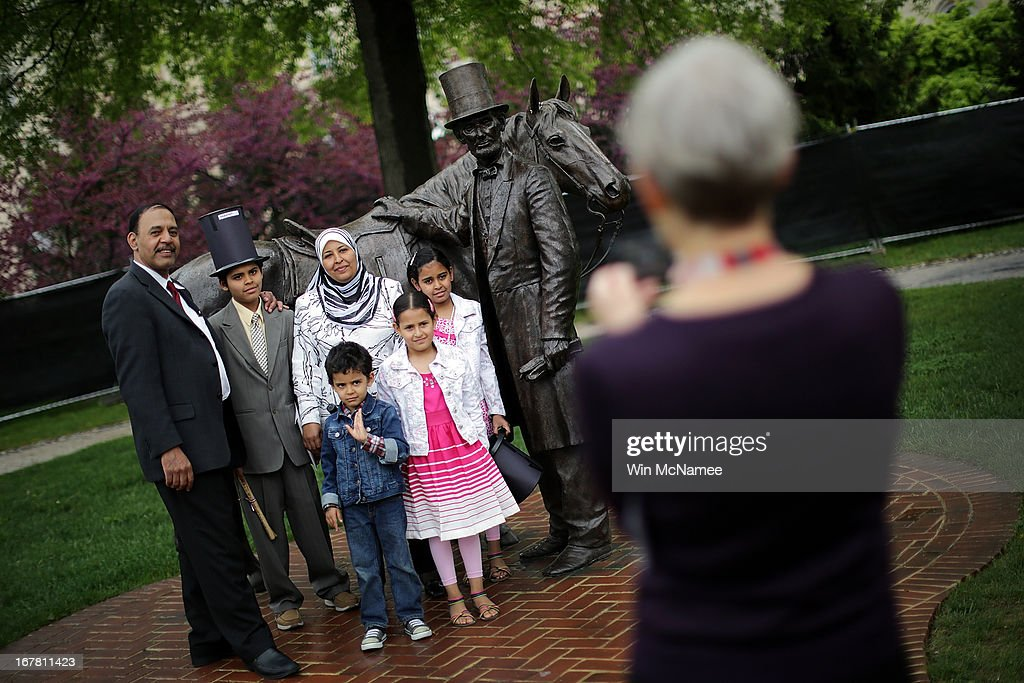 After taking the Oath of Allegiance and becoming U.S. citizens, Abdallah and Nouran Solimen pose for a photo with family members by a statue of U.S. President Abraham Lincoln following a naturalization ceremony in the Emancipation Room at President Lincoln's Cottage April 30, 2013 in Washington, DC. The special citizenship ceremony was hosted by the U.S. Citizen and Immigration Services at the seasonal residence the Lincoln family used during the Civil War and the site where President Lincoln developed the Emancipation Proclamation. From (L-R) are Ahmed Solimen, Abdallah Solimen, Yosef Solimen, Amany Solimen, Nouran Solimen, and Sarah Solimen.