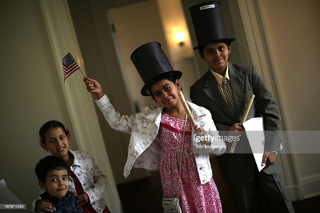 After taking the Oath of Allegiance and becoming U.S. citizens, Abdallah Solimen (R) and Nouran Solimen (2nd R) pose for a photo for their father following a naturalization ceremony for twenty children in the Emancipation Room at President Lincoln's Cottage April 30, 2013 in Washington, DC. The special citizenship ceremony was hosted by the U.S. Citizen and Immigration Services at the seasonal residence the Lincoln family used during the Civil War and the site where President Lincoln developed the Emancipation Proclamation. From (L-R) are Yosef Solimen, Sarah Solimen, Nouran Solimen, and Abdallah Solimen.