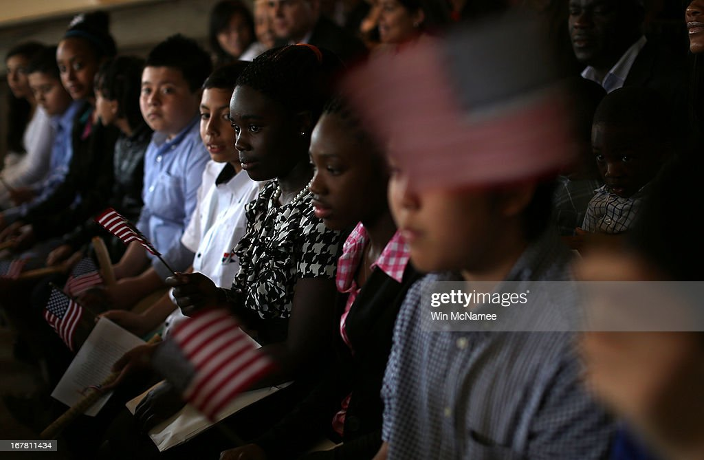 After taking the Oath of Allegiance and becoming U.S. citizens, children wave American flags while listening to 'God Bless the U.S.A.' during a naturalization ceremony in the Emancipation Room at President Abraham Lincoln's Cottage April 30, 2013 in Washington, DC. The special citizenship ceremony was hosted by the U.S. Citizen and Immigration Services at the seasonal residence the Lincoln family used during the Civil War and the site where President Lincoln developed the Emancipation Proclamation.