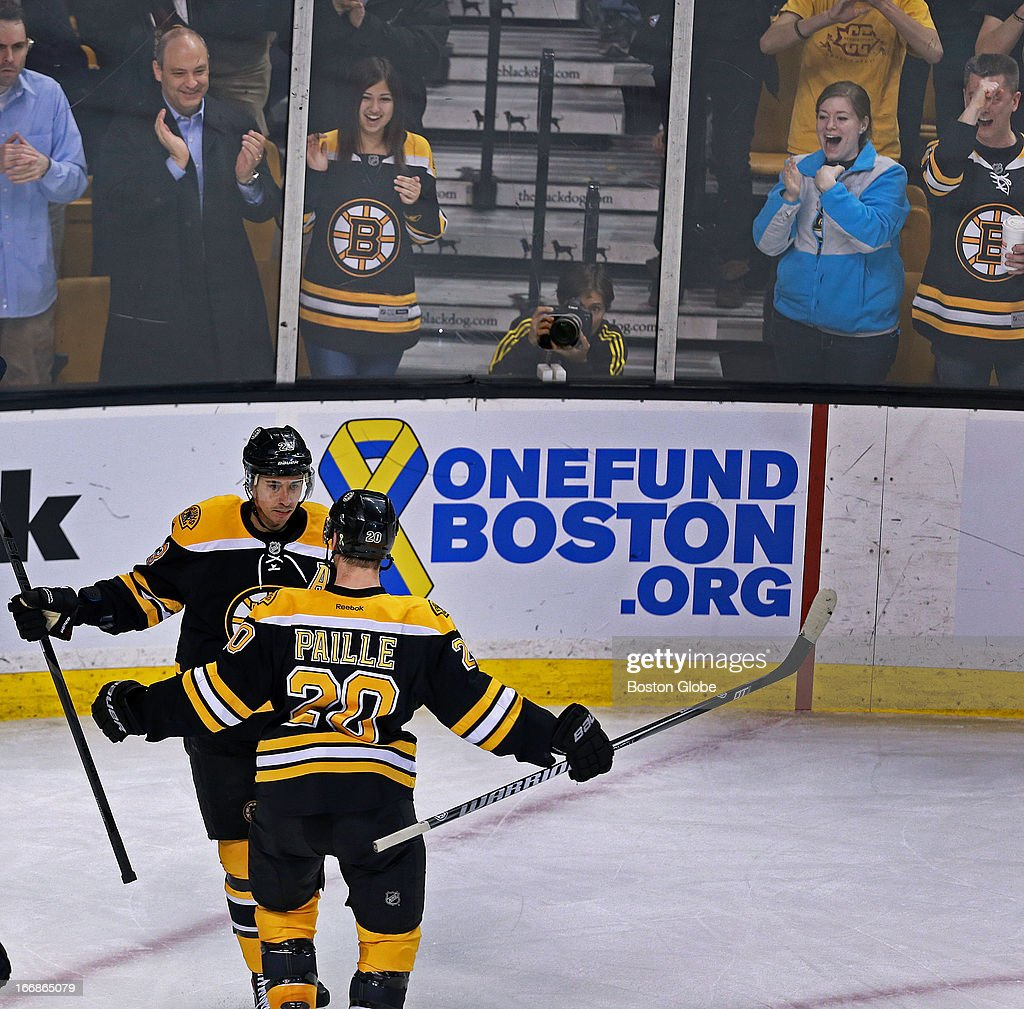 After the Bruins Chris Kelly beat Sabres goalie Ryan Miller to put Boston ahead 2-0 in the second period, he is congratulated by teammate Daniel Paille (#20) who scored Boston's first goal. On the boards behind them is a sign for the 'One Fund Boston' which is raising money for victims of the Boston Marathon bombings. The Boston Bruins hosted the Buffalo Sabres in a regular season NHL game at TD Garden.