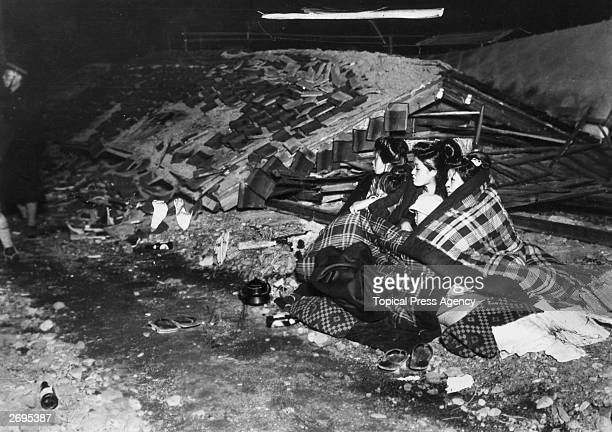 After the disastrous Toyooka earthquake in Japan three women and two young children huddle together under quilted blankets surrounded by debris from...