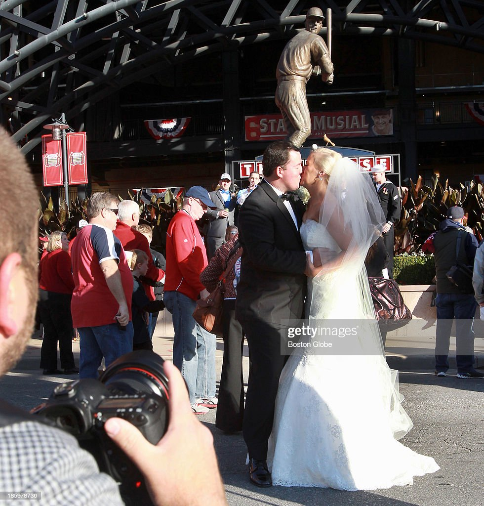 After their wedding, Matt and Caitlin Nahorski stopped by Busch Stadium in St. Louis for photos as crowds gathered for the game. They are from St. Louis, and were among at least two couples who stopped by before the game. Statue of Stan Musial is behind. The St. Louis Cardinals host the Boston Red Sox at Busch Stadium for Game Three of the 2013 Major League Baseball World Series, Oct. 26, 2013.