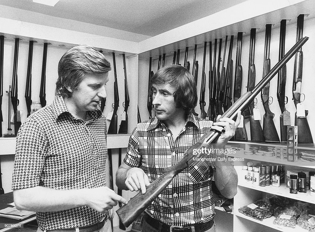 �After trouble with the stock of his gun, Jackie Stewart discusses adjustments with expert Alan Jones�. Three time Formula One racing Champion Sir John Young Stewart OBE, in a gun shop. Before motoracing he made a name for himself in target shooting just missing out on a place at the 1960 Olympics. Stewart became F1 world champion in 1969 in a Matra MS80 car and also suceeded winning the world championship in 1971 and 1973. Stewart retired in 1973 and became a spokesman for safety in F1. He received a knighthood in 2001.