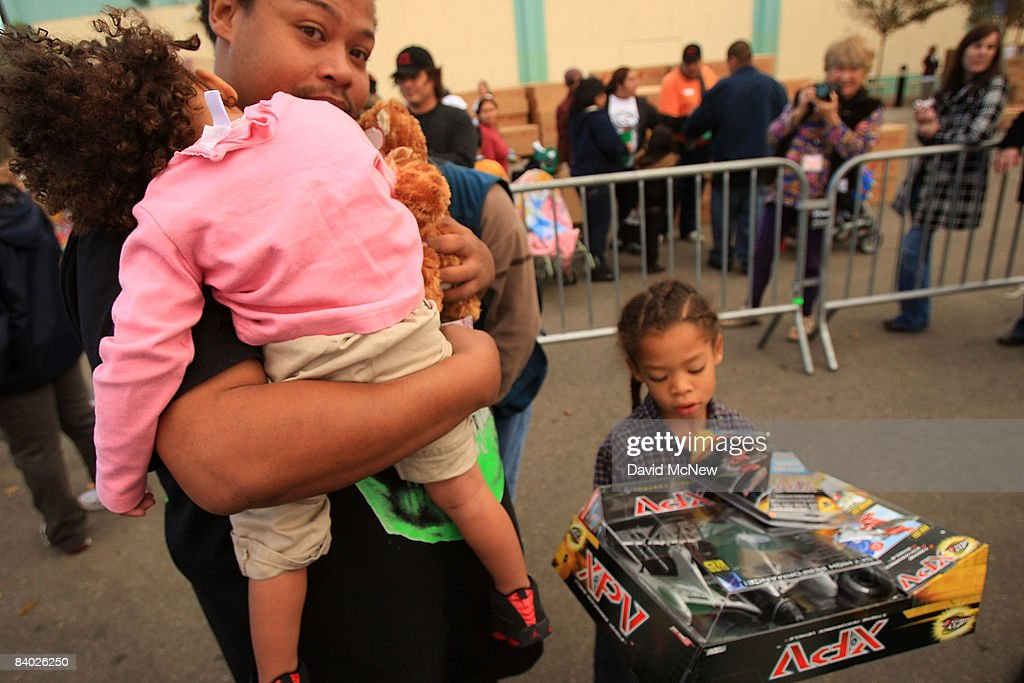 After waiting in a several-blocks-long long line, people receive gifts of food, personal care and household items and toys at the Miracle in South Central event, part of the nationwide Miracle on Main Street, USA program to help working poor and disadvantaged families on December 13, 2008 in the South Central neighborhoods of Los Angeles, California. About 5,000 families are expected to receive enough food at the event to supplement meals for a family of four for a week. Miracle on Main Street, USA is sponsored by The National Basketball Players Association (NBPA) along with Feed The Children, Feed 333, Humanity Unites Brilliance (HUB) and hosted by the Salvation Army.