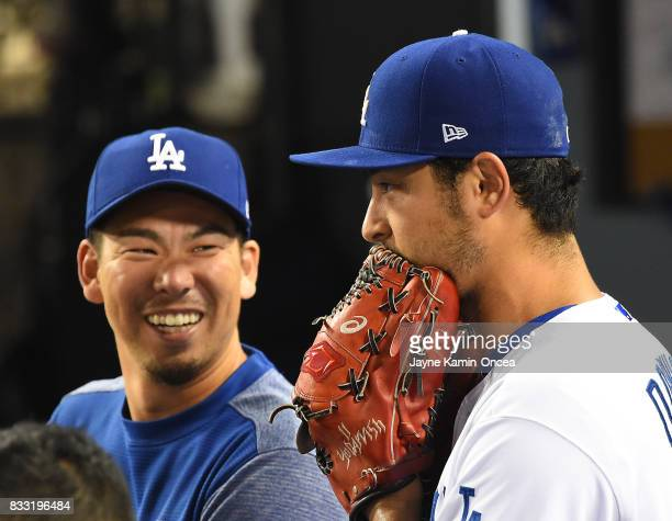 After Yu Darvish of the Los Angeles Dodgers was pulled before the start of the seventh inning he talks with Kenta Maeda in the dugout in the game...