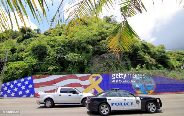 Afternoon traffic passes in front of a wall painted with US and Guam flags in the Tumon district on the island of Guam on August 11 2017...
