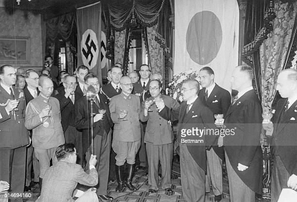 Against a background of their respective flags German and Japanese officials toast the new Axis Pact in Tokyo At extreme right is Heinrich Stahmer...