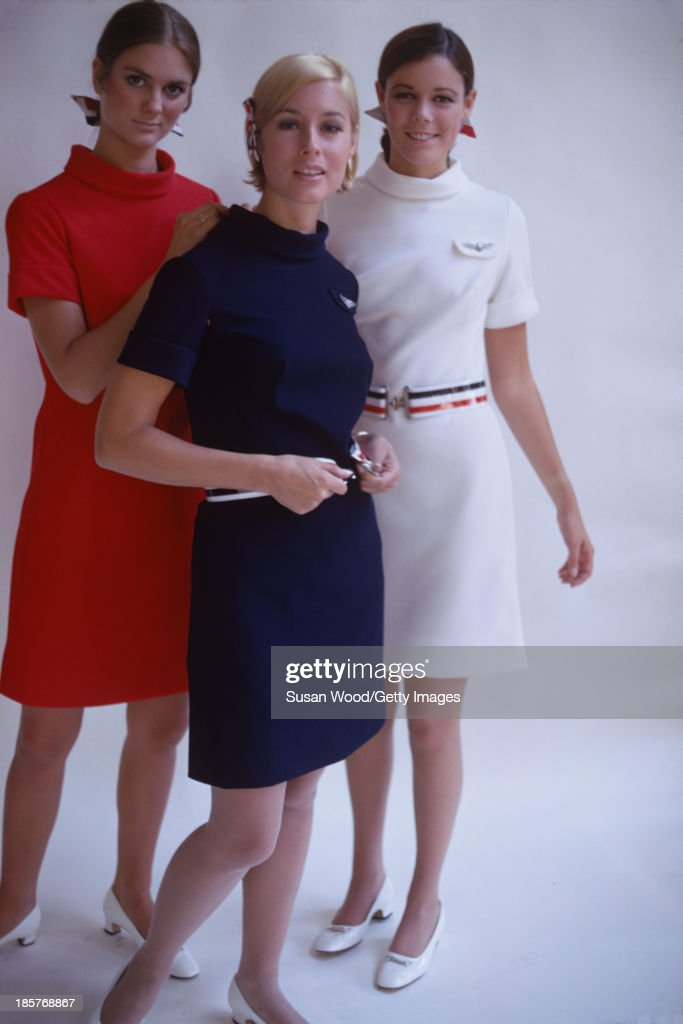Against a white backdrop, a trio of American Airlines air stewardesses help each other into their uniforms, September 1967. The photo was taken as part of a billboard ad campaign for the airline.