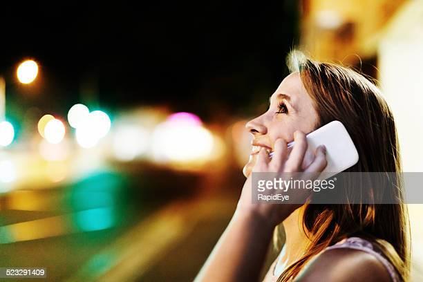 Against motion-blurred street lights, beautiful woman talks on cellphone