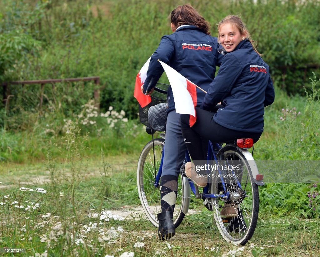 Agata Jodko(R) and Anna Lopato, members of the Polish national eventing team ride a bike holding Polish national flags during European Eventing Championships for Juniors on September 6,2012 in Strzegom.