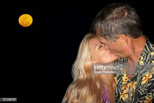 Age difference couple kissing  under a full moon