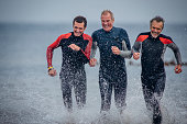 Three mature men running through the sea wearing wetsuits. They are laughing together.