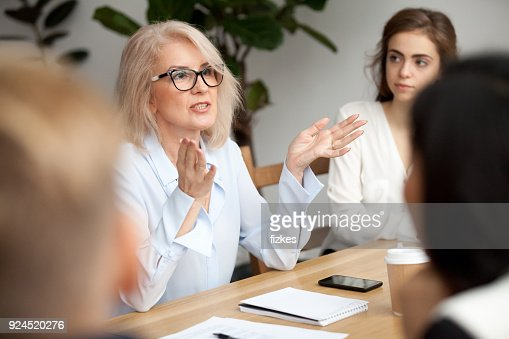 Aged businesswoman, teacher or business coach speaking to young people : Stock Photo