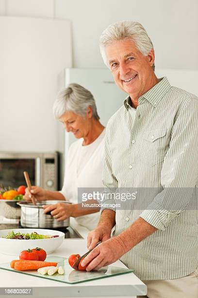 Aged couple preparing food at home